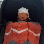 Hanna schläft im Autositz auf dem Weg nach Hause.